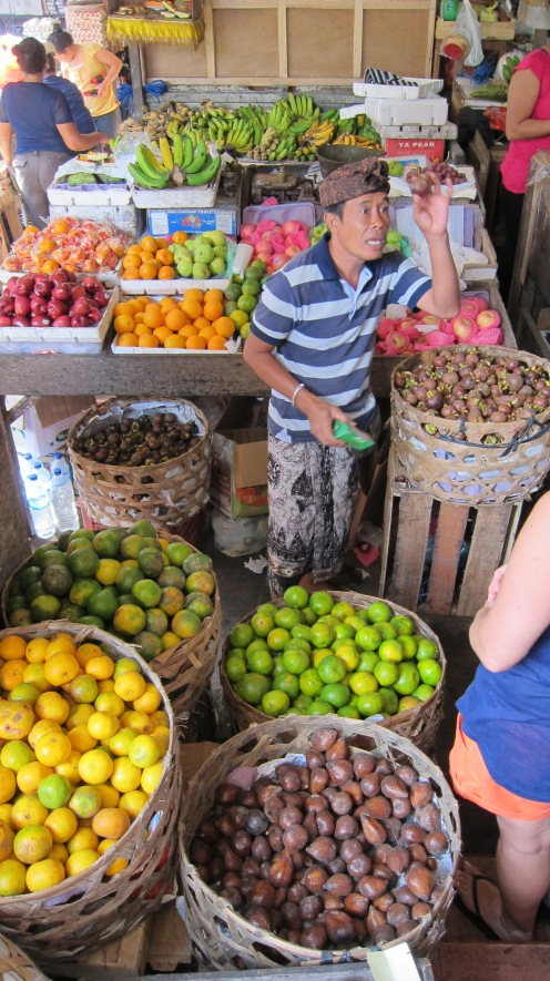 The co-host of our class, Wayan, shows off some of the fruit in the market. He teaches the class with his wife.